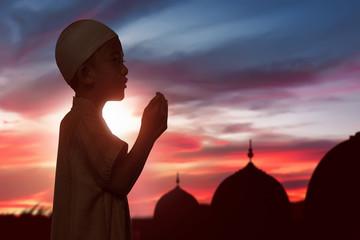 Portrait of asian muslim child raising hand and praying