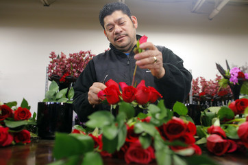 A worker prepares vases of red roses at Winston Flowers in Boston