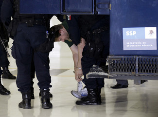 Major drug trafficker Edgar Valdez puts on his shoes before being escorted by Mexican federal police during a news conference at the federal police center in Mexico City
