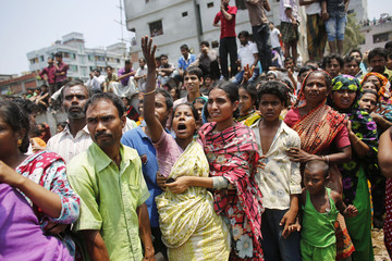 People mourn for their relatives, who are trapped inside the rubble of the collapsed Rana Plaza building, in Savar