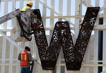 "Workers prepare to remove a sign reading ""No More Weapons""  at the Cordova-Americas international border crossing bridge in Ciudad Juarez"