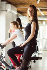 Sport young woman on a stationary bike in the gym