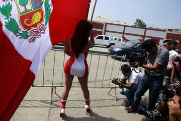 A showgirl holds a Peruvian flag as she poses for photographers outside the sport village during a Peru national soccer team training session in Lima