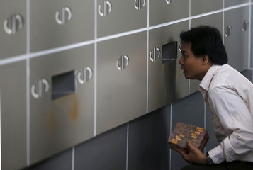An employee of a money changer talks with his colleague through small window while holding a stack of Indonesia rupiah notes in Jakarta