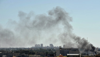 Smoke billows above areas where clashes are taking place between pro-government forces and the Shura Council of Libyan Revolutionaries in Benghazi