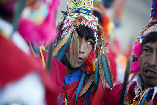 "An Andean dancer wearing a feathered hat waits for the beginning of celebrations in honor of the Lord of ""Qoyllur Rit'i"" near the town of Tayankani in Cuzco"