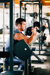 Attractive Young Man Doing Heavy Weight Exercise For Biceps On Machine In A Gym