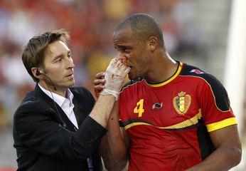 An offical assists Belgium's captain Kompany after a collision with Serbia's goalkeeper Stojkovic during their 2014 World Cup qualifying soccer match at the King Baudouin stadium in Brussels