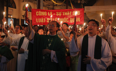 Catholics hold candles during a mass prayer for lawyer Le Quoc Quan at Thai Ha church in Hanoi