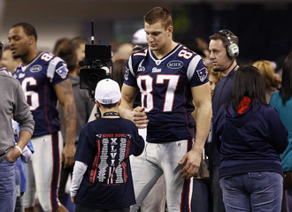 New England Patriots Gronkowski greets a young guest before the NFL Super Bowl XLVI football game in Indianapolis