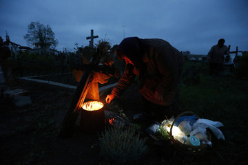 Woman lights a candle at the graves of her relatives at a cemetery in the village of Copaciu