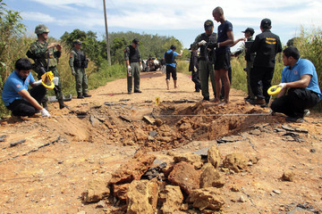 Security personnel inspect the site of a roadside bomb blast in southern Thailand's Pattani province