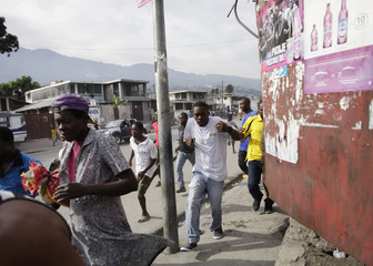 People run after hearing shots during an anti-government protest in Port-au-Prince