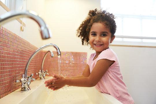 Female Pupil At Montessori School Washing Hands In Washroom