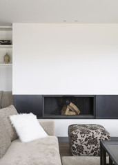 Salon moderne avec cheminée encastrée, canapé en tissu beige, coussin en fourrure blanche et pouf en tissu fleuri
