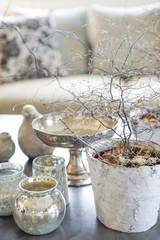 Décoration d'intérieur sur une table basse avec divers vases argentés et pots, céramiques et canapé avec coussins