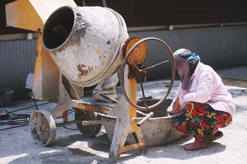 Female laborer worker check mixing cement in basin next to the cement mixer machine