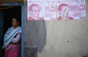 A woman stands at the doorway of her house by a torn election campaign poster of the Chairman of the Unified Communist Party of Nepal at Kritipur in Kathmandu