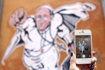 A girl takes a picture of a large drawing  of Pope Francis depicting him as a superhero on a wall near the Vatican
