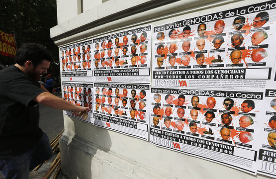 Man puts up posters showing pictures of twenty-one people who are currently on trial for their involvement in kidnapping, torture and murder at La Cacha, illegal detention centre used during Argentina's last dictatorship, in La Plata