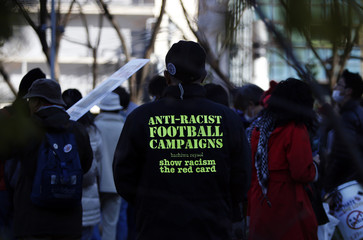An anti-racism protester wearing a jacket with a message stands before a march in Tokyo