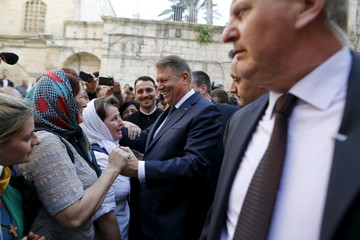 Romanian President Klaus Iohannis meets Christian worshippers outside the Church of the Holy Sepulchre in Jerusalem's Old City
