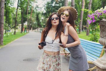 Outdoor portrait of two friends watching photos with a smartphone