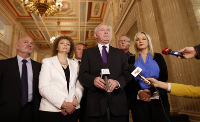 Sinn Fein's Martin McGuinness (C) speaks to the media in Parliament buildings in Belfast Northern Ireland