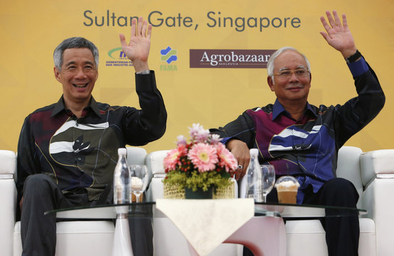 """Singapore's PM Lee and Malaysian counterpart Razak wave as they attend opening ceremony of Malaysia's """"Agrobazaar"""" store, which sells Malaysian agriculture food products, in Singapore"""