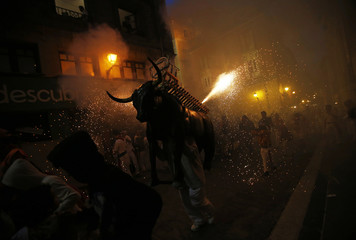 "Revellers are showered with sparks from the ""Fire Bull"", a man carrying a metal structure loaded with fireworks on the fifth day of the San Fermin festival in Pamplona"