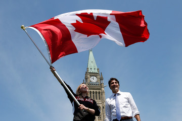 Trampolinist Rosie MacLennan waves the Canadian flag next to PM Justin Trudeau after being named Canada's flag-bearer for the opening ceremony of the 2016 Rio Olympics, on Parliament Hill in Ottawa