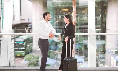 businessman and businesswoman talking at airport
