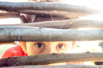 Frightened boy looks at the fence slit