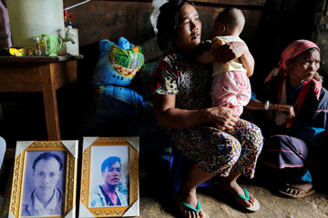 Women sit with a baby, son of one of their killed relatives next to pictures of victims Aik Lu and Aik Sai after their bodies were found in a grave last June at Mong Yaw village in Lashio