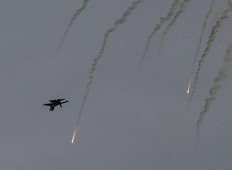 A Ukrainian military aircraft flies as flares are set off near Slaviansk