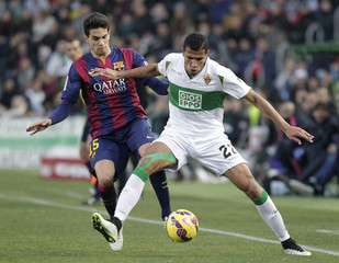 Elche's Jonathas and Barcelona's Bartra fight for the ball during their Spanish first division soccer match at the Martinez Valero stadium in Elche