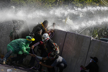 Anti-government protesters take cover behind barricade as policemen use water cannon during clashes with the police the metropolitan police headquarters in Bangkok