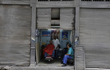A barber works in his shop in Havana