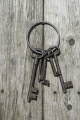 Vintage skeleton keys on a ring over a wooden textured board.