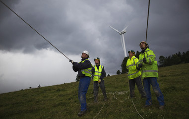 Workers hold cords as a crane lifts a part of a power-generating windmill turbine in a wind farm in Mont Soleil in the Jura region