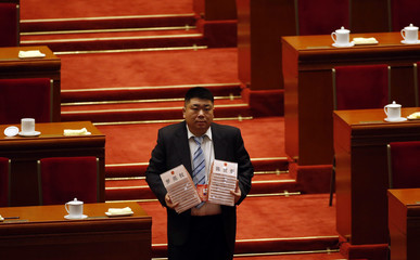 A staff collects name cards after the closing ceremony of the Chinese National People's Congress at the Great Hall of the People, in Beijing
