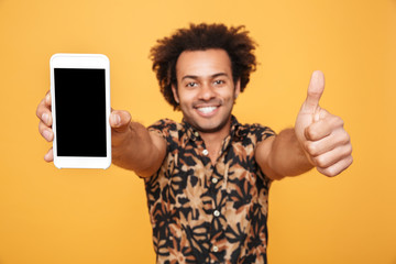 Cheerful young afro american man showing blank screen mobile phone