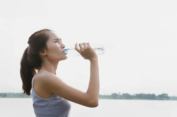 Beautiful women drink bottled water after exercising