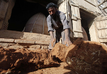 An Afghan man prepares materials for making a tandoor oven used for baking bread in Kabul