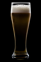 A glass of beer, on a black background, with shiny edges and foam