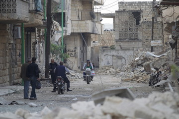 Civilians walk as others ride motorbikes past damaged buildings in the rebel-controlled area of Maaret al-Numan town in Idlib province, Syria
