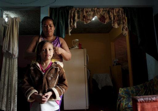 Hazel Castillo combs her daughter Tyra Jaen's hair, at home before going to an aerobics class in Los Guidos de Desamparados