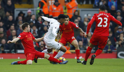 Swansea City's Leroy Fer in action with Liverpool's James Milner and Philippe Coutinho