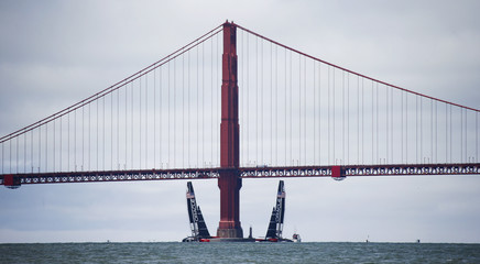 Oracle Team USA AC72 catamarans one and two pass near the Golden Gate Bridge as they train on San Francisco Bay