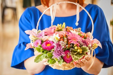 Young and elegant woman holding a flower basket with asters and gerberas in her hands.